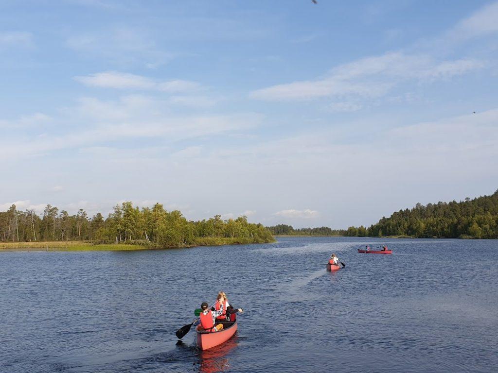 Ihmisiä melomassa kanootilla joella